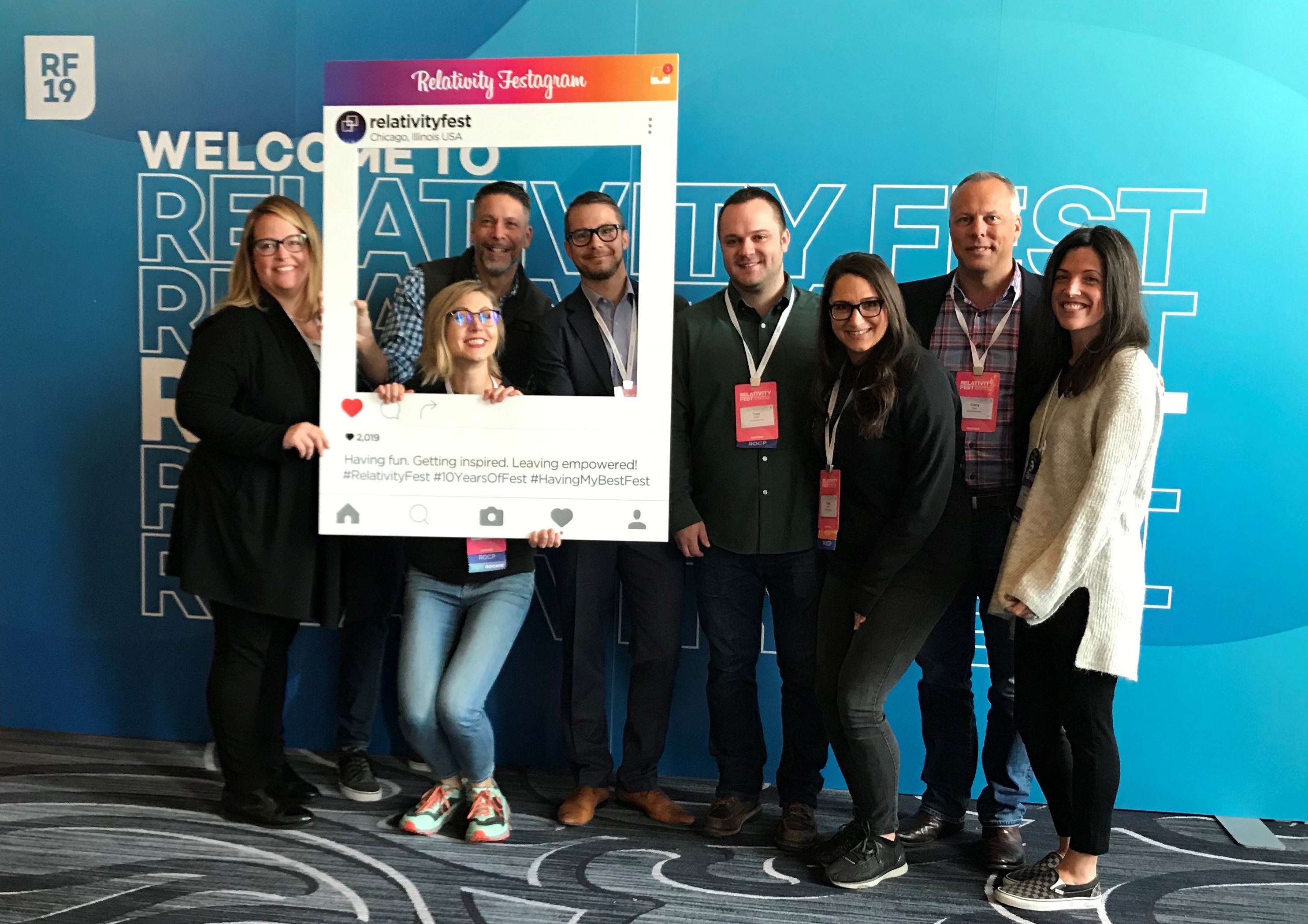 Members of JND eDiscovery team pose for photo at Relativity Fest 2019 marquee.